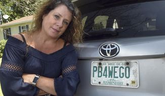 """This Aug. 26, 2019 photo shows Wendy Auger standing by her vehicle in Rochester, N.H.  The state Division of Motor Vehicles asked Auger  to surrender the plate, which reads """"PB4WEGO."""" The division said phrases related to excretory acts aren't permitted. Gov. Chris Sununu said Wednesday, Aug. 28, he reached out to the division and """"strongly urged them"""" to allow Auger to keep the plate. Auger, who was appealing the recall, said """"I'm stoked.""""/Foster's Daily Democrat via AP)"""