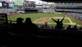 FILE - In this May 15, 2019, file photo, fans cheer during the seventh inning stretch during in the first baseball game of a doubleheader between the New York Yankees and the Baltimore Orioles at Yankee Stadium in New York. The Yankees have reacquired the YES Network, partnering with Amazon.com and the Sinclair Broadcast Group to purchase 80 percent of the station from The Walt Disney Co. Thursday, Aug. 29, 2019, in a deal that values it at $3.47 billion.   (AP Photo/Frank Franklin II)