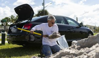 Larry Weiner, from Pembroke Pines, loads bags of sand in preparation for Hurricane Dorian at Jaycee Park, Friday, Aug. 30, 2019 in Hutchinson Island, Fla. Hurricane Dorian was muscling a chaotic path toward Florida, with officials and residents bracing for the possibility it would unleash its full fury early next week but clinging to the glimmer of hope that the strengthening storm could simply skirt the coastline. (Matias J. Ocner/Miami Herald via AP)