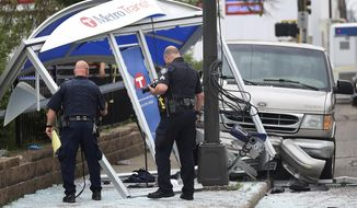 """FILE - In this July 9, 2019, file photo police look over the scene where a van slammed into a crowded bus stop shelter in north Minneapolis. Hennepin County Minnesota, prosecutor Mike Freeman Minnesota prosecutor has charged George Reeves Jensen of Champlin, who crashed his van into a Minneapolis bus shelter, with five counts of criminal vehicular operation. But Hennepin County Attorney Mike Freeman says the injuries resulting from Jensen's driving raise questions about """"more severe charges.""""(David Joles/Star Tribune via AP, File)"""