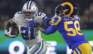 FILE - In this Jan. 12, 2019, file photo, Dallas Cowboys running back Ezekiel Elliott pushes off Los Angeles Rams inside linebacker Cory Littleton during the first half in an NFL divisional football playoff game in Los Angeles. Elliott's holdout clouds the expectations for a franchise longing to return to the Super Bowl for the first time since the last of five championships nearly 25 years ago. The Cowboys have a fourth-year quarterback already with two NFC East titles in Dak Prescott, a receiver ready to show what a full season looks like in Amari Cooper and a defense with an established star in pass rusher DeMarcus Lawrence and two emerging ones in linebackers Jaylon Smith and Leighton Vander Esch. (AP Photo/Mark J. Terrill, File)