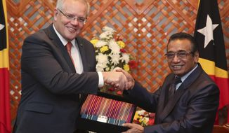 Australian Prime Minister Scott Morrison, left, receives souvenir of traditional Timorese woven cloths called 'tais' from East Timorese President Francisco Guterres during their meeting in Dili, East Timor, Friday, Aug. 30, 2019. Australia has committed to invest in East Timor's naval infrastructure and provide an undersea internet cable between the countries as China increases its influence in the region. (AP Photo/Kandhi Barnez)