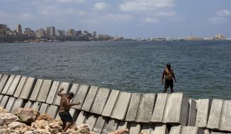 In this Aug. 8, 2019, photo, workers prepare to place cement blocks to reinforce the sea wall against rising water levels on the corniche in Alexandria, Egypt. Alexandria, which has survived invasions, fires and earthquakes since it was founded by Alexander the Great more than 2,000 years ago, now faces a new menace from climate change. Rising sea levels threaten to inundate poorer neighborhoods and archaeological sites, prompting authorities to erect concrete barriers out at sea to hold back the surging waves. (AP Photo/Maya Alleruzzo)