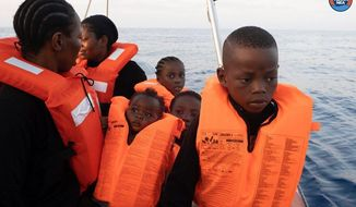 In this Picture made available by the Mediterranea NGO, a group of migrants wear life vests during a rescue operation off the Libyan coasts, Wednesday, Aug. 28, 2019. Italian aid group Mediterranea Charity says a ship it operates has rescued about 100 migrants, including 8 pregnant women and 22 children, and is asking Italian authorities to provide a safe port for them. The Italian NGO tweeted that the rescue happened early on Wednesday, after the Mare Jonio spotted a rubber boat on its radar. (Mediterranean Rescue Via AP)