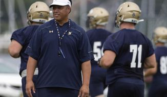 FILE - In this Aug. 2, 2019, file photo, Navy head coach Ken Niumatalolo stands on the field as players warm up during NCAA college football training camp in Annapolis, Md. In the wake of a dismal 2018 season that ended with a disappointing 3-10 record, Navy head coach Ken Niumatalolo made sweeping changes. The result of the overhaul will be on full display Saturday when the Midshipmen open a new season at home against Holy Cross.(AP Photo/Tommy Gilligan, File)