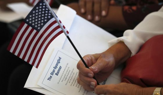 In this Aug. 16, 2019, file photo a citizen candidate holds an American flag and the words to The Star-Spangled Banner before the start of a naturalization ceremony at the U.S. Citizenship and Immigration Services Miami field office in Miami. (AP Photo/Wilfredo Lee) ** FILE **