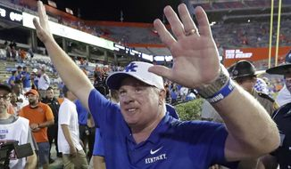 FILE - In this Sept. 8, 2018, file photo, Kentucky head coach Mark Stoops waves to fans after defeating Florida 21-16 during the second half of an NCAA college football game, in Gainesville, Fla. Mark Stoops will receive an annual raise of $500,000 plus incentives over the remaining six years of a restructured contract following the Wildcats' best season in 41 years. The seventh-year coach will earn $4.75 million this season with increases up to $6 million in 2024-25. (AP Photo/John Raoux, File)