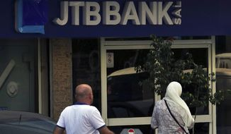 "People enter a branch of Jammal Trust Bank in Beirut, Lebanon, Friday, Aug. 30, 2019. The Lebanese bank targeted by the U.S. Department of the Treasury for ""knowingly facilitating banking activities"" for the militant Hezbollah group has denied the charges, saying it abides by international laws. (AP Photo/Bilal Hussein)"