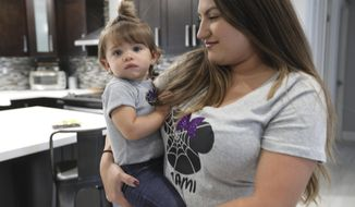 In this Thursday, Aug. 29, 2019 photo, Jessica Armesto holds her one-year-old daughter, Mila's, at their home in Miami. Jessica was hoping that Mila could meet a real-life Minnie Mouse at Disney World before Hurricane Dorian derailed her plans. The U.S. National Hurricane Center says Hurricane Dorian could hit the Florida coast over the weekend as a major hurricane. (AP Photo/Marcus Lim)