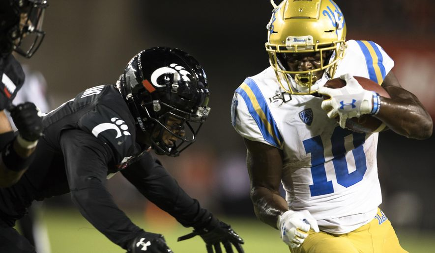 Cincinnati safety Darrick Forrest forces UCLA wide receiver Demetric Felton (10) out of bounds during the second half of an NCAA college football game Thursday, Aug. 29, 2019, in Cincinnati. (Albert Cesare/The Cincinnati Enquirer via AP)