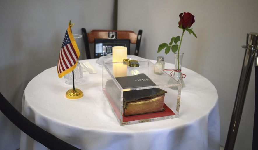 """FILE - This  May 6, 2019 photo provided by the Manchester VA Medical Center shows a Bible as part of a memorial table display at the veterans hospital in Manchester, N.H.  Vice President Mike Pence has weighed in on a First-Amendment lawsuit challenging a Bible on display at a New Hampshire veterans hospital, saying under the current administration, """"VA hospitals will not be religion-free zones."""" Pence addressed the American Legion National Convention in Indianapolis on Wednesday, Aug. 28. He said """"The Bible stays."""" (Kristin Pressly/Manchester VA Medical Center via AP)"""