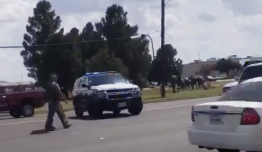 "In this image made from video provided by Dustin Fawcett, police officers guard on a street in Odessa, Texas, Saturday, Aug. 31, 2019. Police said there are ""multiple gunshot victims"" in West Texas after reports of two suspects opening fire on Saturday in the area of Midland and Odessa. (Dustin Fawcett via AP)"