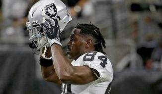 FILE - In this Aug. 15, 2019, file photo, Oakland Raiders wide receiver Antonio Brown (84) puts on his helmet prior to the team's NFL football game against the Arizona Cardinals in Glendale, Ariz. Brown missed significant practice time dealing with frost-bitten feet suffered while getting cryotherapy treatment in France and waging a battle with the NFL over the use of his outdated helmet. He lost a grievance to allow him to use the helmet that's no longer certified as safe and returned to camp. (AP Photo/Rick Scuteri, File)
