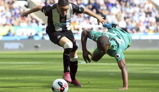 Newcastle United's Miguel Almiron, left, and Watford's Christian Kabasele battle for the ball during the English Premier League soccer match at St James' Park, London, Saturday Aug. 31, 2019. (Owen Humphreys/PA via AP)