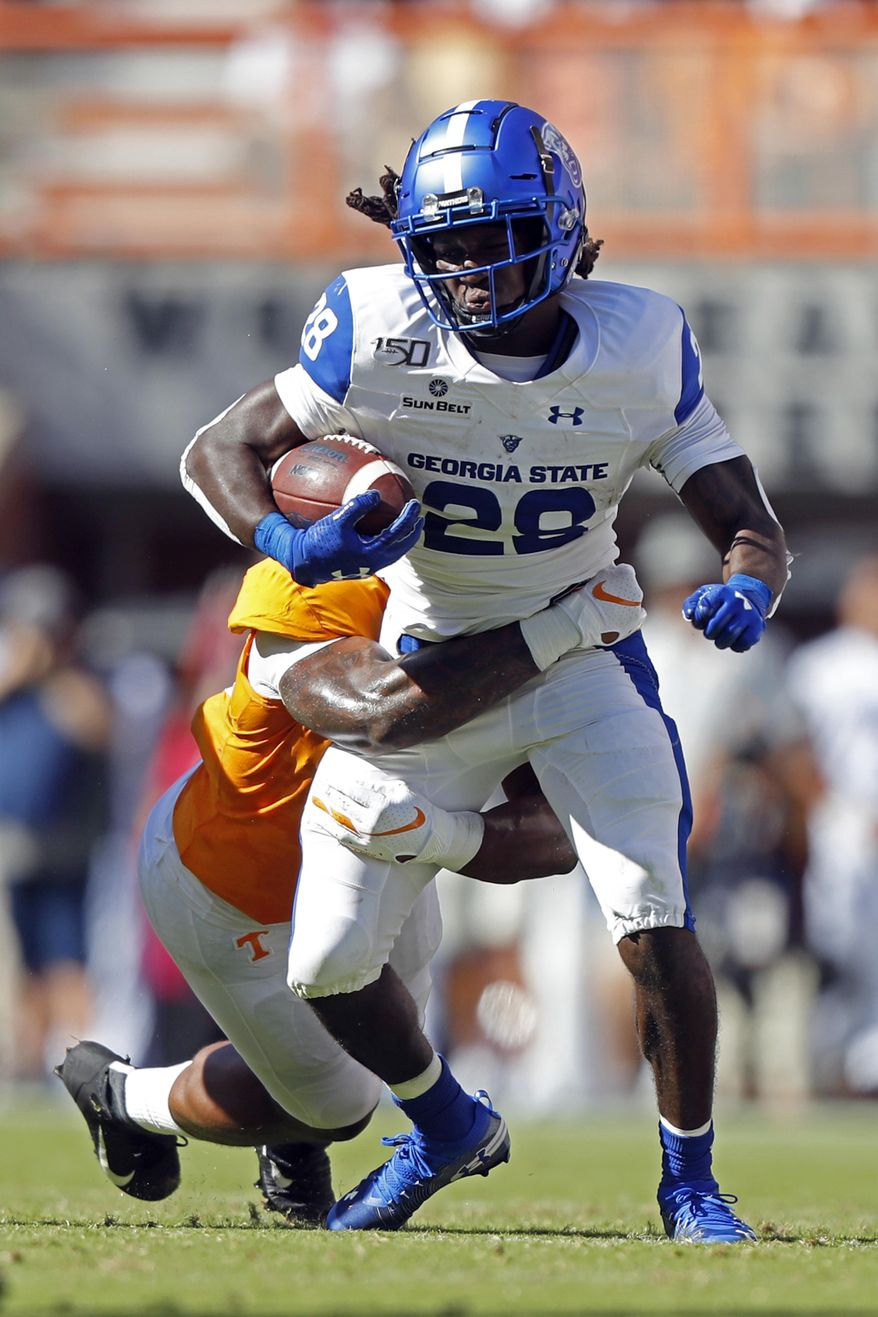 Georgia State running back Seth Paige (28) tries to escape the grasp of a Tennessee defender in the first half of an NCAA college football game Saturday, Aug. 31, 2019, in Knoxville, Tenn. (AP Photo/Wade Payne)