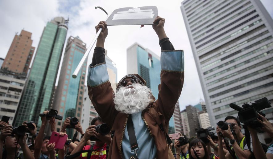 A protester dressed as legendary biblical figure Moses with a mock tablet attends a pro-democracy protest in Wan Chai, Hong Kong, Saturday, Aug. 31, 2019. Hundreds of people are rallying in an athletic park in central Hong Kong as a 13th-straight weekend of pro-democracy protests gets underway. (AP Photo/Jae C. Hong)