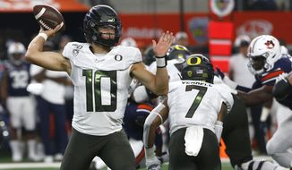 Oregon quarterback Justin Herbert (10) looks to throw against Auburn during the first half of an NCAA college football game, Saturday, Aug. 31, 2019, in Arlington, Texas. (AP Photo/Ron Jenkins)