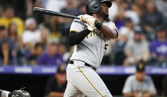 Pittsburgh Pirates' Josh Bell follows the flight of his solo home run off Colorado Rockies relief pitcher Wes Parsons in the fourth inning of a baseball game, Saturday, Aug. 31, 2019, in Denver. (AP Photo/David Zalubowski)