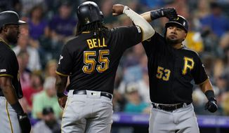 Pittsburgh Pirates' Melky Cabrera, right, celebrates a three-run home run against the Colorado Rockies with Josh Bell (55) during the fifth inning of a baseball game, Friday, Aug. 30, 2019, in Denver. (AP Photo/Jack Dempsey)