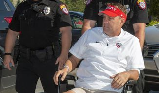 Liberty head football coach Hugh Freeze arrives to coach from a wheelchair in the coaches' box against Syracuse in an NCAA college football game in Lynchburg, Va., Saturday, Aug. 31, 2019. (AP Photo/Matt Bell)