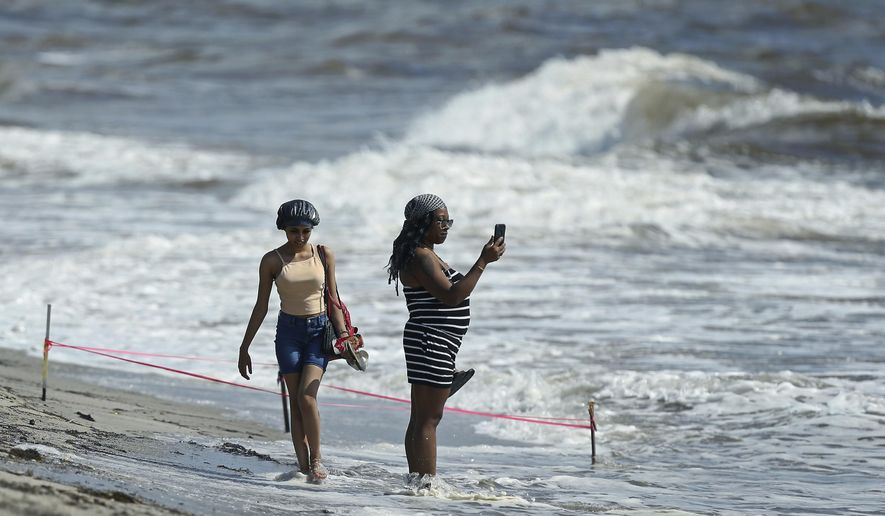 A beachgoer takes pictures at the beach on Saturday, Aug. 31, 2019 in Dania Beach in Florida. The latest forecast says Hurricane Dorian is expected to stay just off shore of Florida and skirt the coast of Georgia, with the possibility of landfall still a threat on Wednesday, and then continuing up to South Carolina early Thursday.  (David Santiago/Miami Herald via AP)