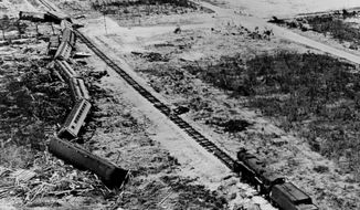 In this undated photo made available by the Keys History & Discovery Center, shows a derailed train and surrounding devastation caused by a Labor Day hurricane in 1935. The hurricane is still the most powerful to strike the U.S. More than two dozen hurricanes have made landfall in the U.S. over the same holiday weekend since 1851. Hurricane Dorian is expected near the Florida coast this weekend. (Keys History & Discovery Center via AP)