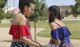 In this photo taken Aug. 23, 2019, Julia Huebert, 13 , and Kaitlin Huebert 12, play at the Metro Verde Splash Pad park in Las Cruces, New Mexico. The sisters attend Pecos Connections Academy, a tuition free online school. (Bethany Freudenthal/Las Cruces Sun-News via AP)