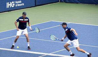 Mike Bryan, left, returns a shot as his brother Bob Bryan, looks on during a first round doubles match against Hubert Hurkacz, of Poland, and Vasek Pospisil, of Canada, at the US Open tennis championships Friday, Aug. 30, 2019, in New York. (AP Photo/Sarah Stier)