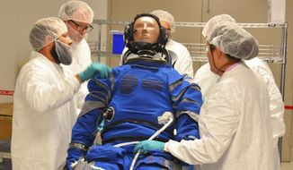 Inside the Boeing facility at Kennedy Space Center, engineers and technicians fit the the anthropometric test device- the test dummy- into a space suit. The test dummy will fly on the orbital flight test of the CST-100 Starliner. Malcom Denemark/Florida Today via AP)