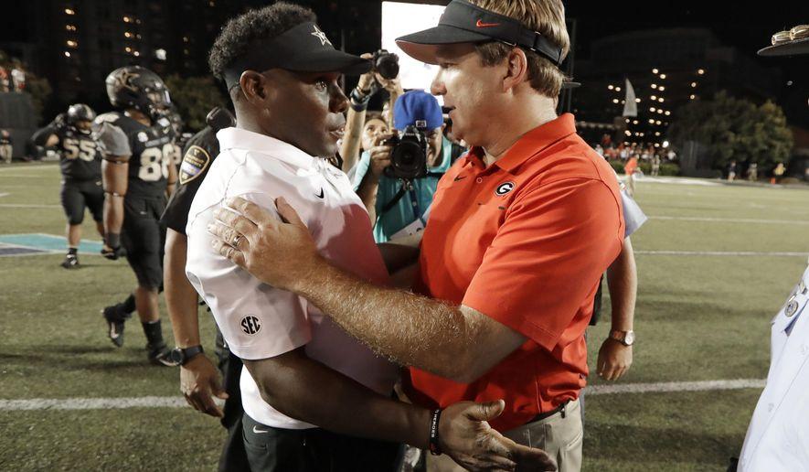 Vanderbilt head coach Derek Mason, left, congratulates Georgia head coach Kirby Smart after an NCAA college football game Saturday, Aug. 31, 2019, in Nashville, Tenn. (AP Photo/Mark Humphrey)