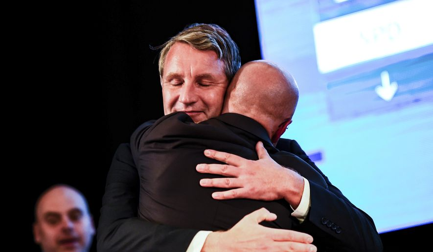 Top candidate of right-wing party Alternative for Germany, AfD, for the elections at the federal state Brandenburg Andreas Kalbitz, right, is embraced by AfD Thuringia chairman Bjoern Hoecke at an election party in Werder, near Potsdam, Sunday, Sept. 1, 2019. The citizens of the German federal states Saxony and Brandenburg elected their new parliament. ( Gregor Fischer/dpa via AP)