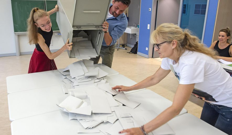 Election workers open one of the ballot boxes during the procedure for counting votes in a polling station, the secondary school Buehlau, in Dresden, eastern Germany, Sunday, Sept. 1, 2019. The citizens of the German states Saxony and Brandenburg elected their new parliament during this day. (AP Photo/Jens Meyer)