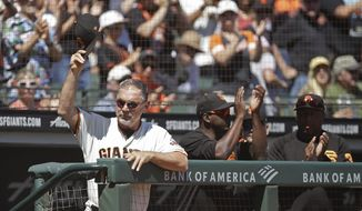 San Francisco Giants manager Bruce Bochy, left, tips his cap to fans after artwork on the left field wall dedicated to him was unveiled during the baseball game against the San Diego Padres Sunday, Sept. 1, 2019, in San Francisco. Bochy will retire from Major League baseball at the end of the 2019 season. (AP Photo/Ben Margot)