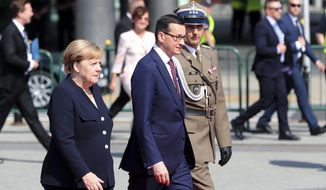 German Chancellor Angela Merkel, left, arrives with Polish Prime Minister Mateusz Morawiecki for a memorial ceremony marking the 80th anniversary of the start of World War II in Warsaw, Poland, Sunday, Sept. 1, 2019.(AP Photo/Czarek Sokolowski)
