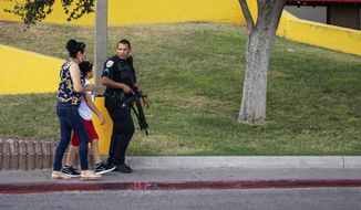An Odessa police officer escort bystanders away from an area investigated for a shooting in Odessa, Texas, Saturday, Aug. 31, 2019, following a deadly shooting. Several people were dead after a gunman who hijacked a postal service vehicle in West Texas shot more than 20 people, authorities said Saturday. The gunman was killed and a few law enforcement officers were among the injured. (Jacy Lewis/Reporter-Telegram via AP)