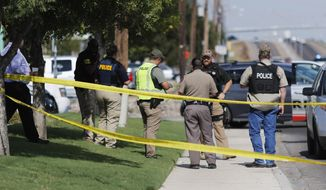 Authorities cordon off a part of the sidewalk in the 5100 block of E. 42nd Street in Odessa, Texas, Saturday, Aug. 31, 2019. (Mark Rogers/Odessa American via AP)