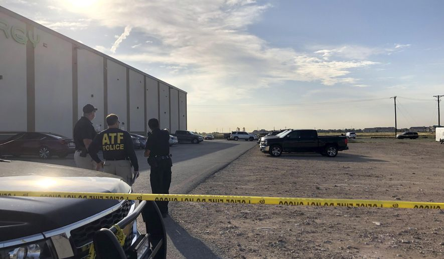 Bureau of Alcohol, Tobacco, Firearms and Explosives agents speak with a local police officer in a gravel lot next to an Odessa, Texas, movie theater Sunday, Sept. 1, 2019, where authorities say the suspected shooter in Saturday's rampage was killed.  The death toll in the West Texas shooting rampage increased to Sunday as authorities investigated why a man stopped by state troopers for failing to signal a left turn opened fire on them and fled, shooting over a dozen people as he drove before being killed by officers outside a movie theater. (AP Photo/Jake Bleiberg)