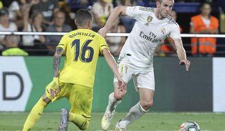 Real Madrid's Gareth Bale, vies withe Villareal's Xavi Quintilla during the Spanish La Liga soccer match between Villarreal and Real Madrid in the Ceramica stadium in Villarreal, Spain, Sunday, Sept. 1, 2019. (AP Photo/Alberto Saiz)
