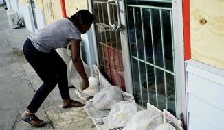 Yolande Rolle puts sandbags at her shop's doorstep as she prepares for the arrival of Hurricane Dorian in Freeport on Grand Bahama, Bahamas, Sunday, Sept. 1, 2019. Hurricane Dorian intensified yet again Sunday as it closed in on the northern Bahamas, threatening to batter islands with Category 5-strength winds, pounding waves and torrential rain. (AP Photo/Ramon Espinosa)