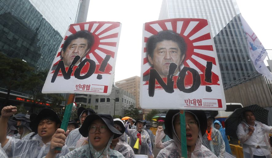 "South Korean protesters with images of Japanese Prime Minister Shinzo Abe shout slogans during a rally to mark the South Korean Liberation Day from Japanese colonial rule in 1945, in front of the Japanese Embassy in Seoul, South Korea, Thursday, Aug. 15, 2019. South Korean President Moon Jae-in on Thursday offered an olive branch to Japan to end a tense trade dispute, saying Seoul will ""gladly join hands"" if Tokyo to accepts calls to resolve it through dialogue. (AP Photo/Ahn Young-joon)"