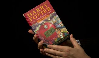 """Sotheby's director of the department of printed books and manuscripts Dr Philip Errington poses for photographers with a first edition copy of the first Harry Potter book """"Harry Potter and the Philosopher's Stone"""" containing annotations and illustrations by author J.K. Rowling, during a photocall organized for the media at the auction house's premises in London, Monday, May 20, 2013. The book will be offered for sale as part of the """"First Editions, Second Thoughts"""" auction on May 21, for which there are no price estimates available in advance as it is a charity sale. (AP Photo/Matt Dunham)"""