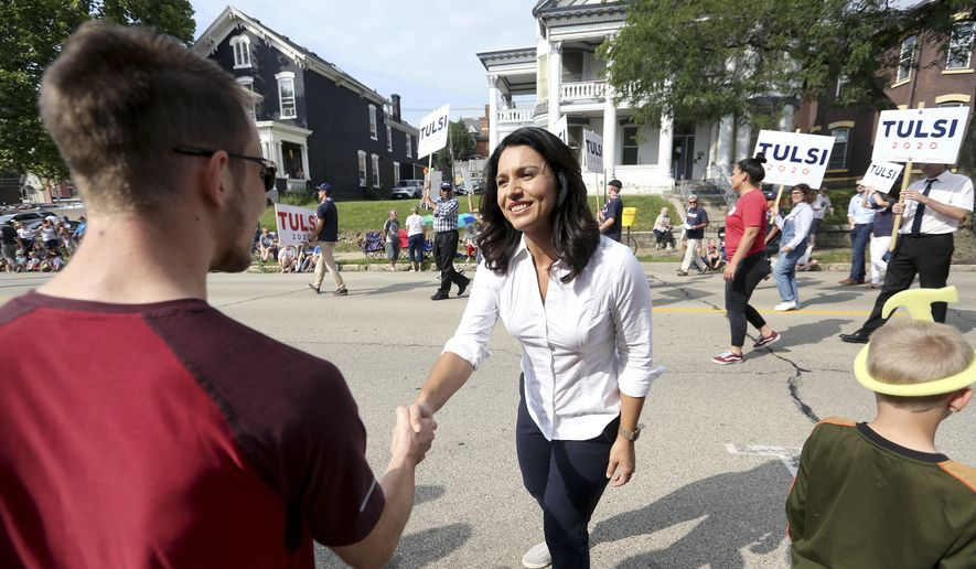 Democratic presidential candidate U.S. Rep. Tulsi Gabbard, D-Hawaii, greets people during Dubuque's Labor Day parade in Dubuque, Iowa, on Monday, Sept. 2, 2019. (Jessica Reilly/Telegraph Herald via AP)