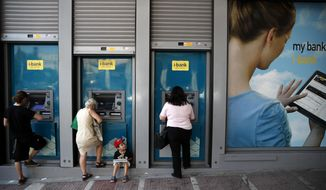 People use the ATMs of a bank in central Athens, Monday, Aug. 26, 2017.  Greece's prime minister Kyriakos Mitsotakis says the country will soon lift the last remaining restrictions imposed on bank depositors more than four years ago at the height of the country's financial crisis. (AP Photo/Thanassis Stavrakis)