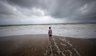 Weston Lee, of Vero Beach, stands near the high surf from the Atlantic Ocean, in advance of the potential arrival of Hurricane Dorian, in Vero Beach, Fla., Monday, Sept. 2, 2019. (AP Photo/Gerald Herbert)