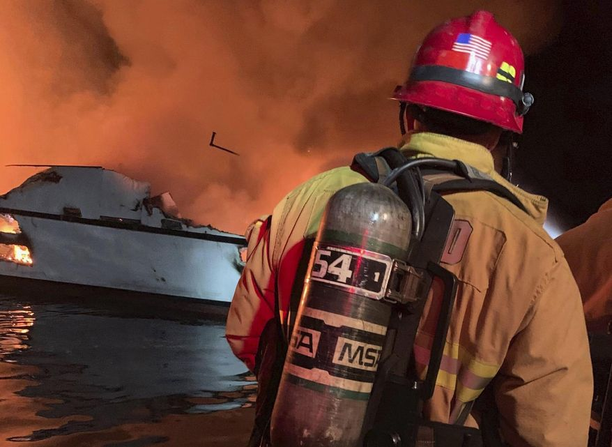 """In this photo provided by the Ventura County Fire Department, VCFD firefighters respond to a boat fire off the coast of southern California, Monday, Sept. 2, 2019. The U.S. Coast Guard said it has launched several boats to help over two dozen people """"in distress"""" off the coast of southern California. (Ventura County Fire Department via AP)"""