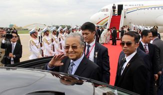 In this photo provided by Agence Kampuchea Presse (AKP), Malaysian Prime Minister Mahathir Mohamad, center, waves to Cambodian government officers upon his arrival at Phnom Penh International Airport, Monday, Sept. 2, 2019, in Phnom Penh, Cambodia. Mahathir has arrived in Cambodia for a three-day official visit to strengthen the two countries' bilateral relationship. (Khem Sovannara, Agence Kampuchea Presse via AP)
