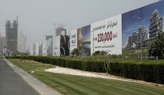 FILE - In this June 6, 2018 file photo, billboards advertise luxury villas and apartments in Dubai, United Arab Emirates. Dubai's ruler has issued a directive to curb the pace of new real estate construction projects amid falling demand and property prices. On Monday, Sept. 2, 2019, Sheikh Mohammed bin Rashid Al Maktoum ordered the creation of a committee to study the needs of the real estate market, evaluate all future projects and control the pace of projects so supply does not outstrip demand. (AP Photo/Kamran Jebreili, File)