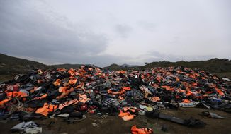 FILE - In this Thursday, March 16, 2017 file photo, piles of life jackets used by refugees and migrants are left in Molyvos village, on the northeastern Greek island of Lesbos. About 1,500 asylum-seekers were being transported from Greece's eastern Aegean island of Lesbos to the mainland Monday Sept. 2, 2019, as part of government efforts to tackle massive overcrowding in refugee camps and a recent spike in the number of people arriving from the nearby Turkish coast. (AP Photo/Thanassis Stavrakis, File)