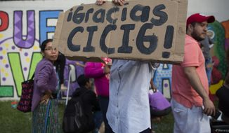 "An activist holds a sing that reads in Spanish ""Thanks CICIG"" at the United Nations International Commission Against Impunity headquarters in Guatemala City, Saturday, Aug. 31, 2019. The UN mission is closing its operation after 12 years. It brought to trial three former presidents and hundreds of businessmen, officials, judges and individuals accused of corruption in the Central American country. (AP Photo/Moises Castillo)"