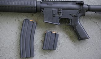 In this April 10, 2013, file photo, a stag arms AR-15 rifle with 30 round, left, and 10 round magazines is displayed in New Britain, Conn.  (AP Photo/Charles Krupa, File) **FILE**